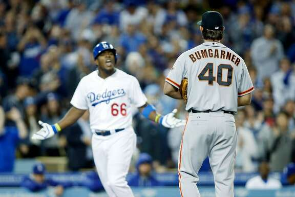 San Francisco Giants starting pitcher Madison Bumgarner, right, and Los Angeles Dodgers' Yasiel Puig, left, exchange words as Puig runs down the third base line after hitting a solo home run during the sixth inning of a baseball game, Friday, May 9, 2014, in Los Angeles. (AP Photo/Danny Moloshok)