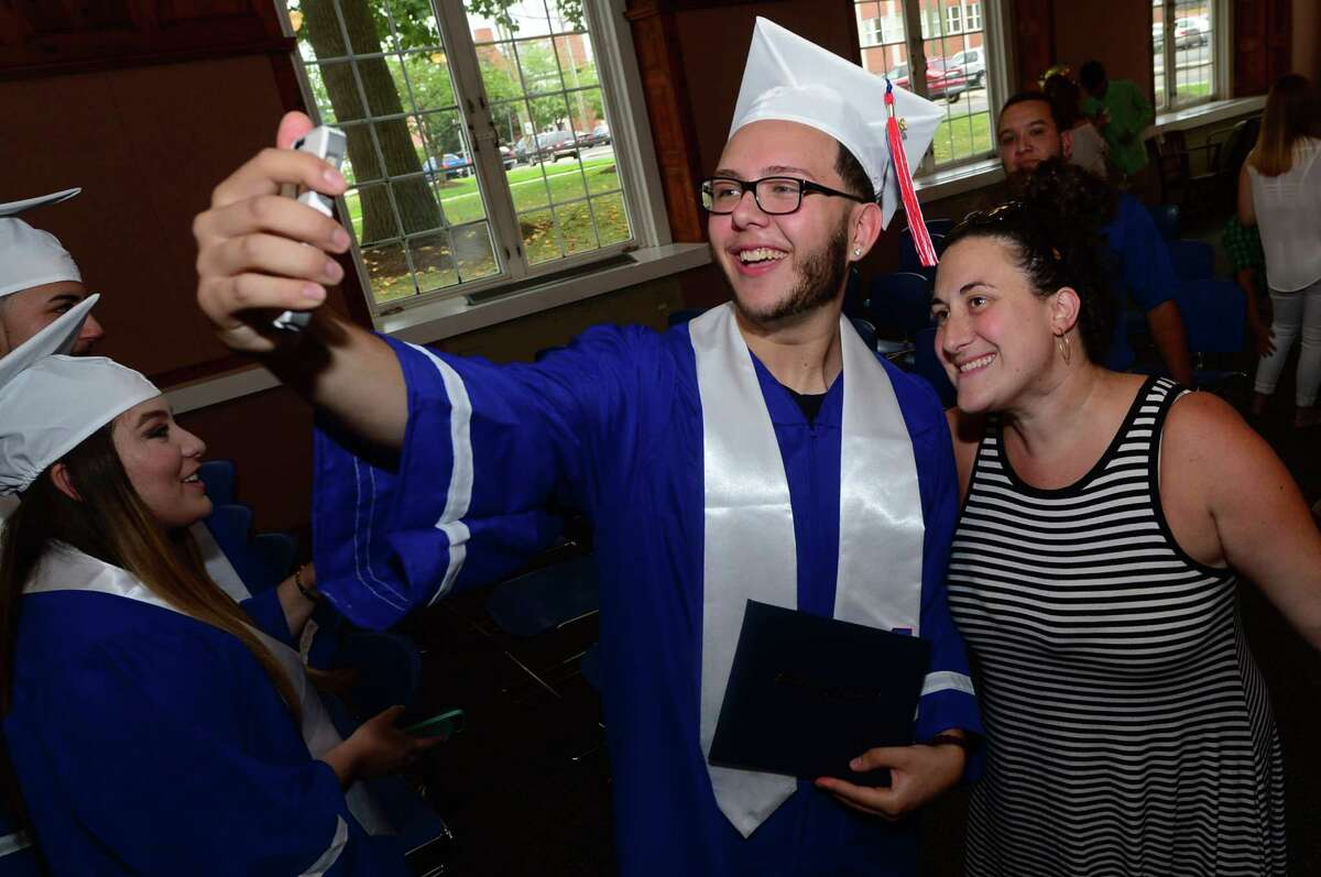 Brien McMahon High School senior Eric Vento celebrates with his English teacher, Sarah Molinelli, as students from both high schools receive their diplomas during the Norwalk Public School's summer school program graduation exercises for the Class of 2016 at the City Hall Community Room in Norwalk on Tuesday, Aug. 2.