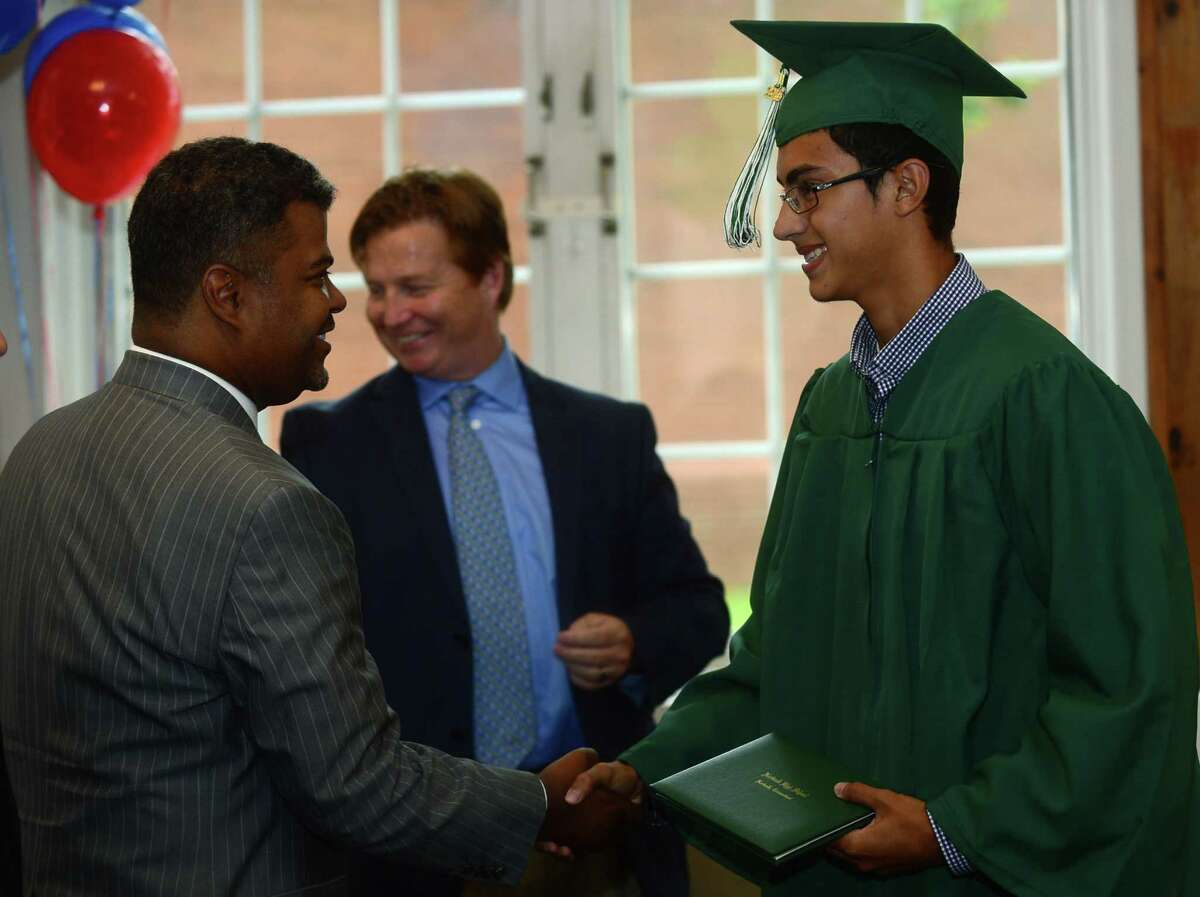 Norwalk High School senior Jurguens Barrantes is congratulated by Board of Education member, Dr. Yvel Crevecoeur, as students from both high schools receive their diplomas during the Norwalk Public School's summer school program graduation exercises for the Class of 2016 at the City Hall Community Room in Norwalk on Tuesday, Aug. 2.