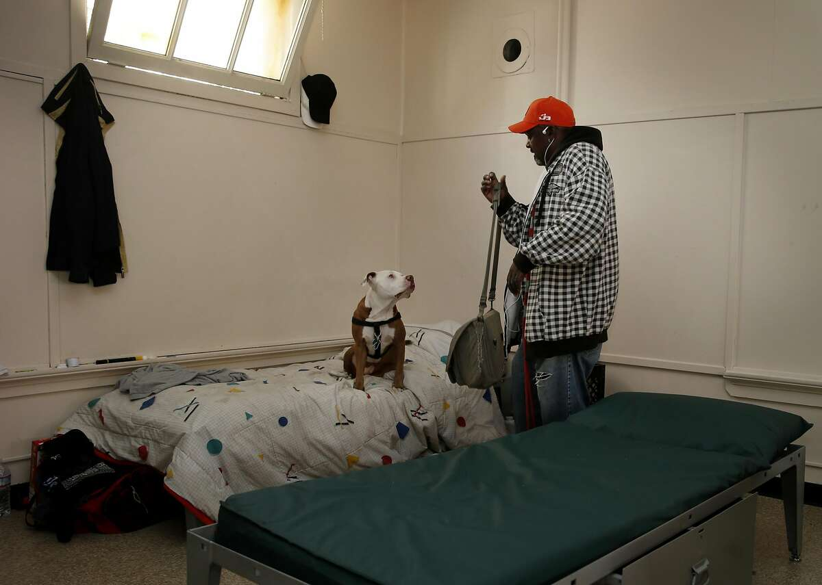 Rodney O'Neill, a homeless man and his dog sleep on a cot in one corner of a large building on the facility Thursday April 16, 2015. The San Francisco, Calif. homeless navigation center is now in operation in the Mission district where they hope to move entire encampments into the facility and help the people find housing and other supportive programs.