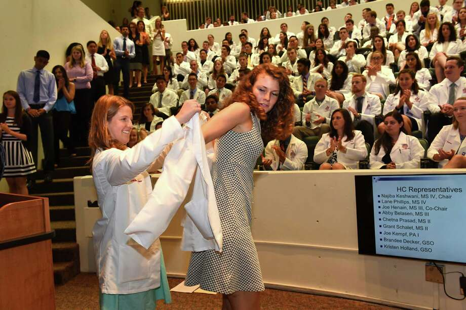 New medical student Betsy Stevens from Averill Park, right, receives her white lab coat from second year student Dorothea Letner of Boston during the traditional white coat ceremony at Albany Medical College on Tuesday, Aug. 2, 2016 in Albany, N.Y. Stevens is in the Siena joint degree program. (Lori Van Buren / Times Union) Photo: Lori Van Buren / 20037506A