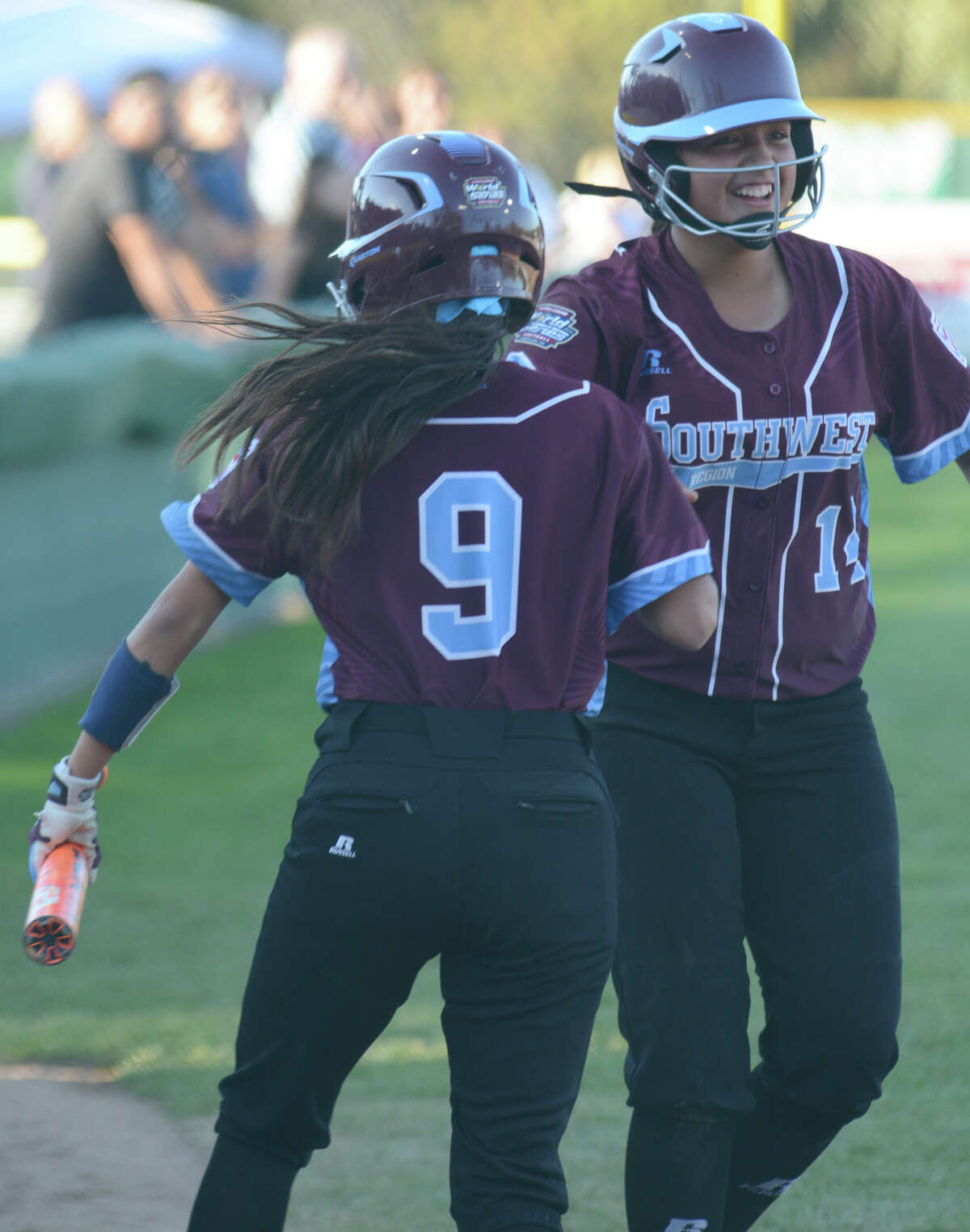 Annika Litterio, 14, greets Avery Ranger on her way back to the dugout after Ranger scored the game's first run on a single to right field by Jada Munoz.
