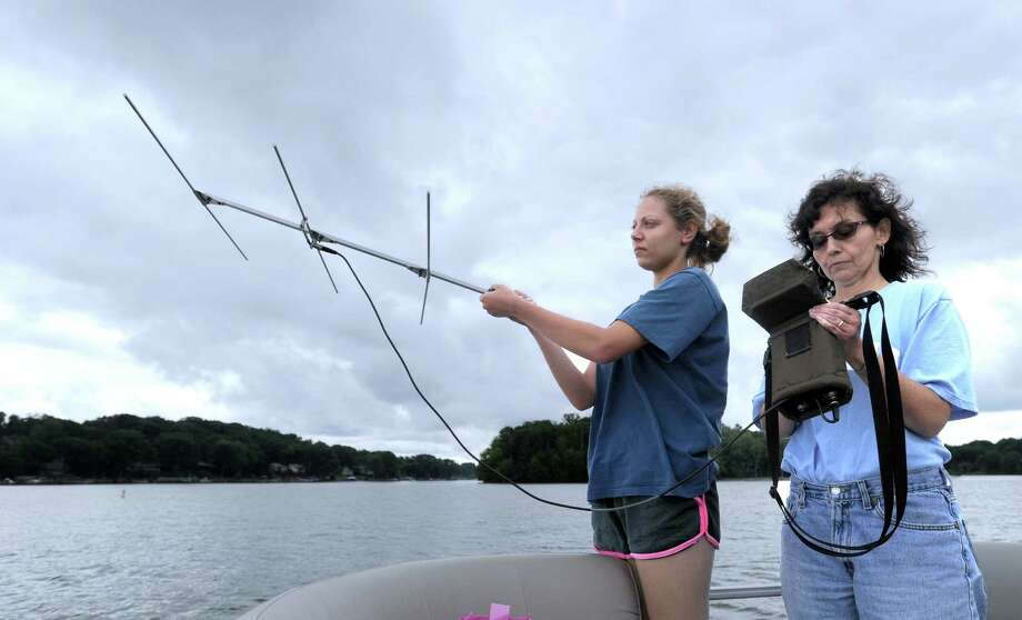 Michelle Bissett, left, an intern at the Great Hollow Wilderson School, and Theodora Pinou, a bioloy professor at Western Connecticut State University, use an antena to detect the frequency assosciated with various sterile grass carp released in June. This will help them track the movement of the fish throughout Candlewood Lake. Photo Tuesday, August 2, 2016. Photo: Carol Kaliff / Hearst Connecticut Media / The News-Times