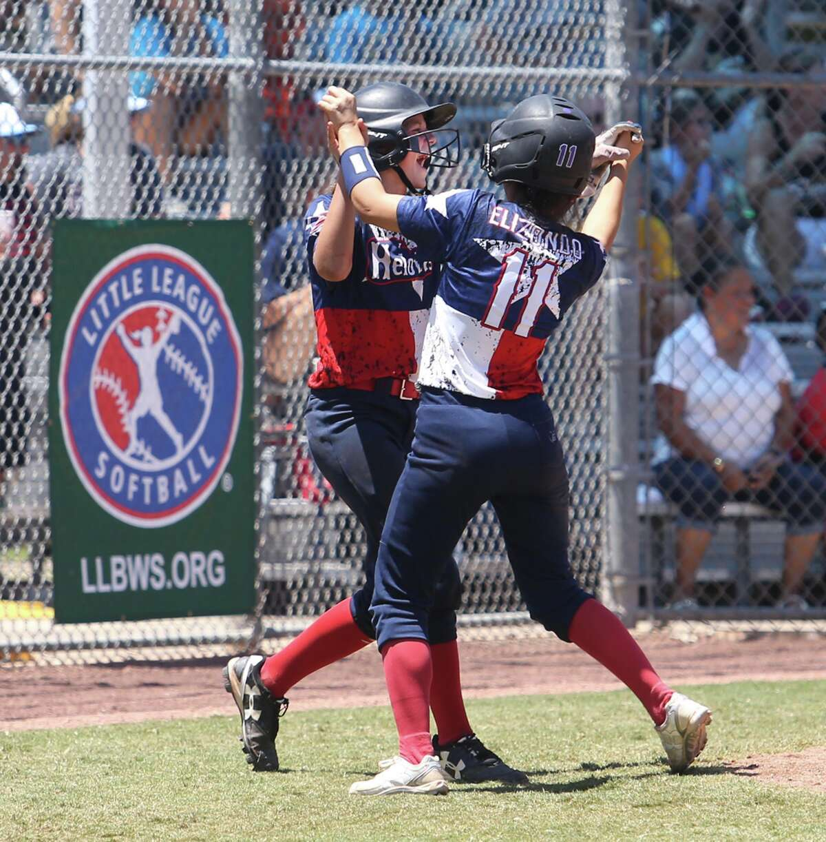 Arianna Elizondo-Galvan (right) and Jacqueline Kirkpatrick meet after scoring to put Greater Helotes ahead in the fifth inning.