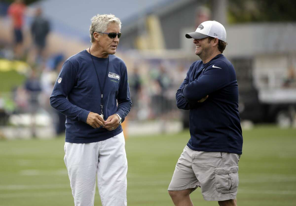 Seattle Seahawks head coach Pete Carroll, left, and general manager John Schneider talk during the team's NFL football training camp Saturday, July 30, 2016, in Renton, Wash. (AP Photo/Elaine Thompson)