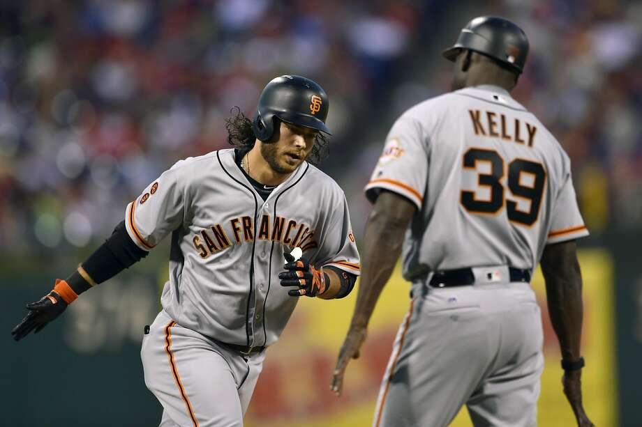 Brandon Crawford prepares to hand-slap third-base coach Roberto Kelly after his fourth-inning homer. Photo: Derik Hamilton, Associated Press