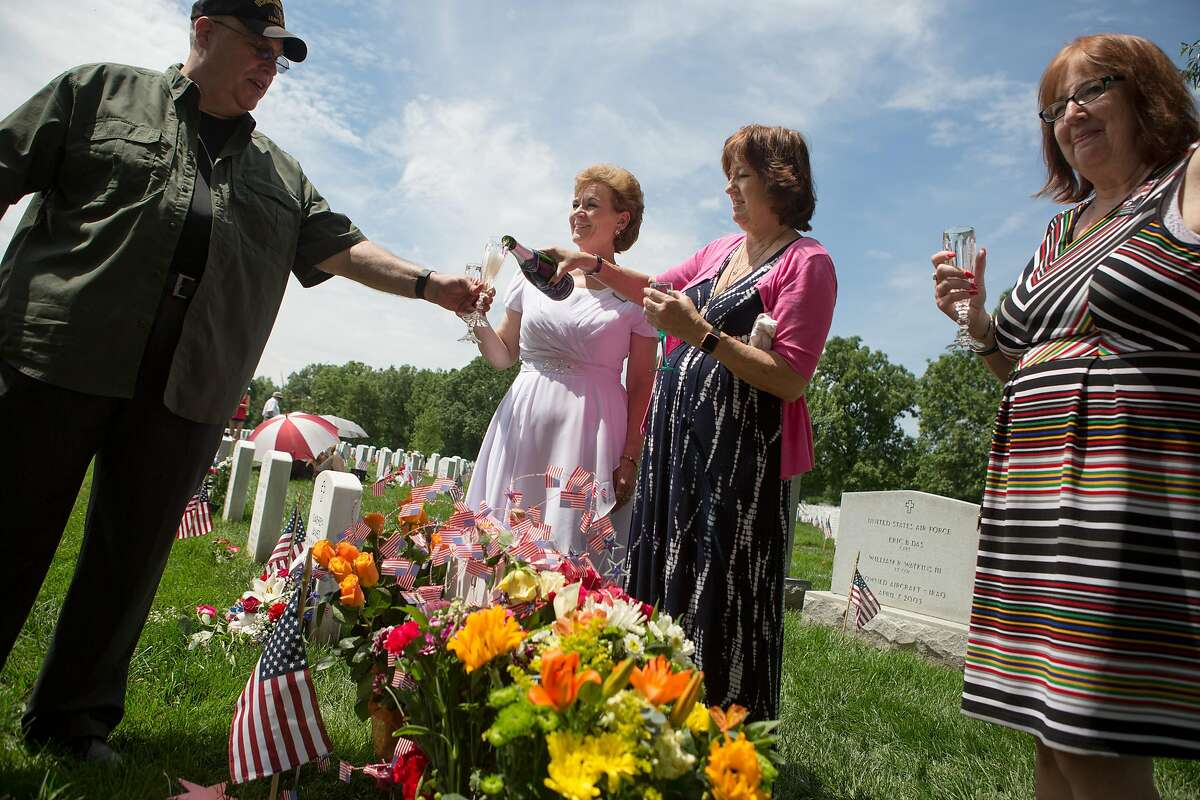 ARLINGTON, VA - MAY 30: Karen Meredith of Mountain View, California, pours champagne for a friend as Vickie Castro, left, and Cathy Patton, a retired military nurse, join her around the grave of Meredith's son/Patton's nephew Lt. Kenneth Ballard in Section 60, the burial ground for military personnel killed since 2001, at Arlington National Cemetery on May 30, 2016 in Arlington, Virginia. Both Ballard and Castro's son Jonathan were killed in Iraq in 2004. The women have been gathering with others at the grave every year since to celebrate their lives. (Photo by Allison Shelley/Getty Images)