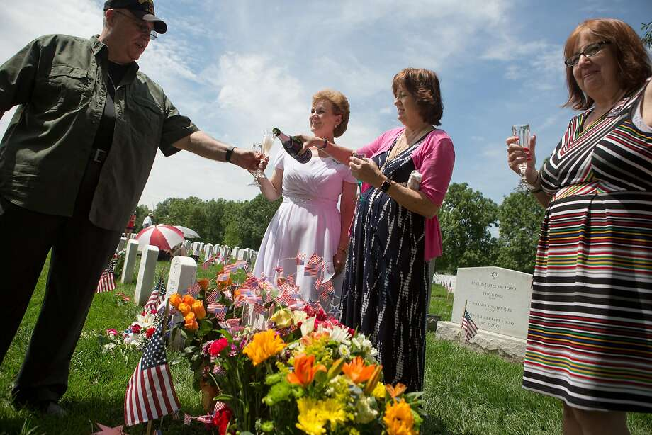 Karen Meredith pours Champagne while celebrating teh life of her son Lt. Kenneth Ballard at Arlington Cemetery on Memorial Day. Photo: Allison Shelley, Getty Images