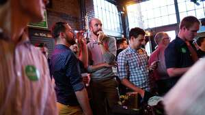A supporters of 7th Congressional District senate candidate Brady Walkinshaw watch as opponent Pramila Jayapal gives a speech on television after taking a strong initial lead in the Washington primary at Comet Tavern on Tuesday, Aug. 2, 2016.