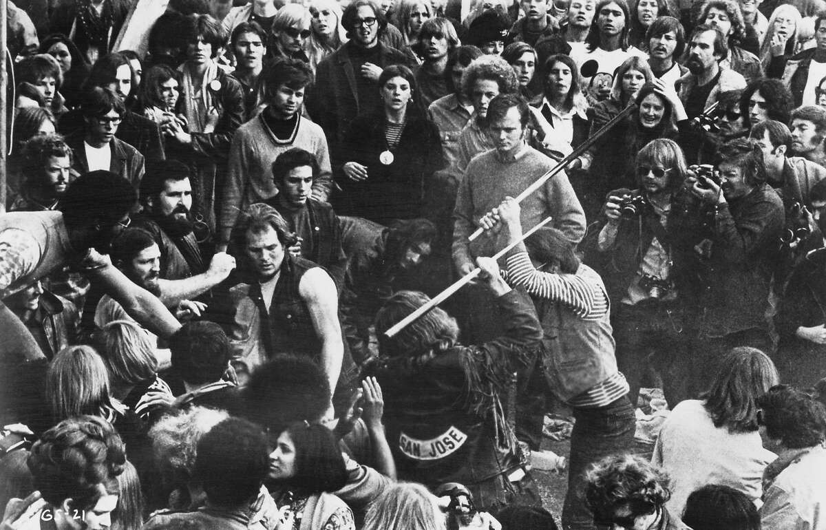 A still from the documentary film 'Gimme Shelter', showing audience members looking on as Hells Angels beat a fan with pool cues at the Altamont Free Concert, Altamont Speedway, California, 6th December 1969. The concert was headlined and organized by The Rolling Stones. The film was directed by Albert Maysles, David Maysles and Charlotte Zwerin. (Photo by 20th Century Fox/Michael Ochs Archives/Hulton Archive/Getty Images)