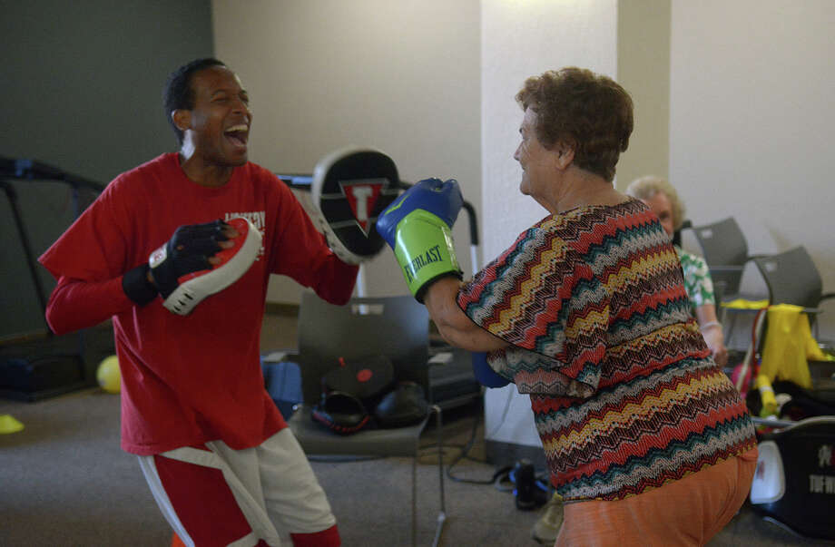 Trainer Jay Robinson, left, spars with Betty Demerat during his Boxercise class in the fitness center at Arbor Terrace at Kingwood Town Center. Robinson said boxing builds self confidence and core body strength in the senior citizens. Photo: Jerry Baker, Freelance / Freelance