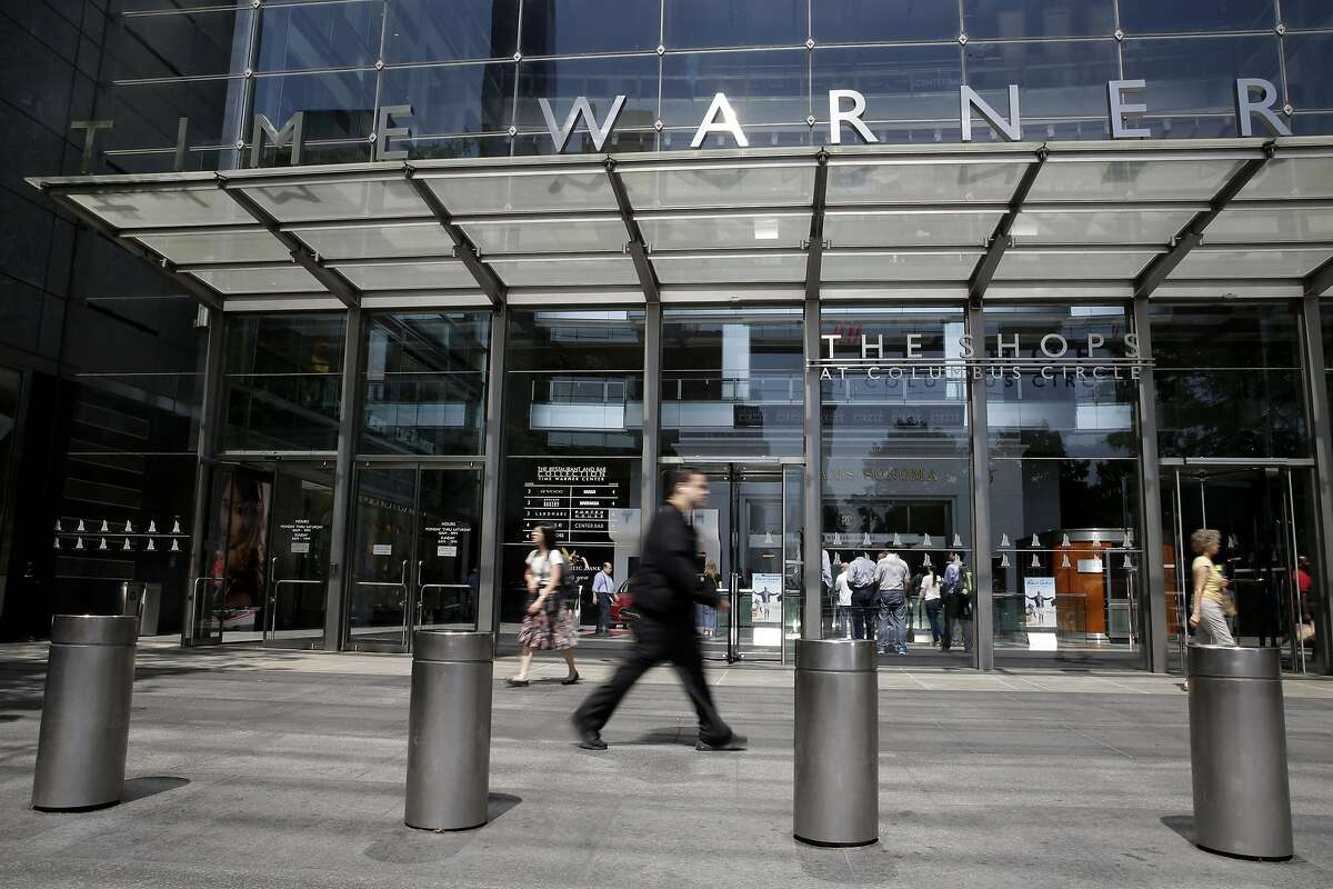 FILE - In this Tuesday, May 26, 2015, file photo, pedestrians walk past the Time Warner Center, home of the headquarters of Time Warner Cable, in New York. On Wednesday, Aug. 3, 2016, Time Warner Inc. reports financial results. (AP Photo/Mary Altaffer, File)