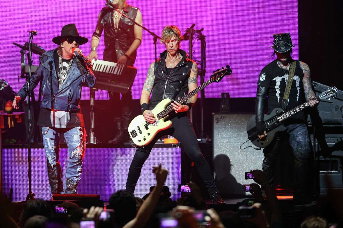 FILE - In this April 23, 2014 file photo, Axl Rose, from left, Duff McKagan and DJ Ashba of Guns N' Roses perform on stage at the 6th Annual Revolver Golden Gods Award Show at Club Nokia in Los Angeles. Crowds thronged for tickets after a surprise announcement that Guns N' Roses would play a concert Friday night, April 1, 2016, at West Hollywood's famed Troubadour music venue. The band announced on its website and in a press release that a limited number of tickets at a very old-school price of $10 apiece would be available at noon at the former location of the famous Tower Records store on the Sunset Strip. (Photo by Paul A. Hebert/Invision/AP, File)