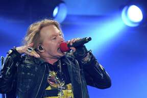"""(FILES) This file photo taken on May 13, 2016 shows US singer Axl Rose performing on stage with Australian band AC/DC on May 13, 2016 in Marseille, southern France.  On their long-awaited reunion tour, Guns N' Roses have largely avoided the antics that once made the band so notorious -- but not entirely. Frontman Axl Rose said that the hard rock legends were briefly detained in Canada for trying to bring in a gun.""""Yeah, we found a gun,"""" he told a sold-out crowd July 16, 2016 at the Rogers Centre arena in Toronto, according to a video posted online afterward by a fan.  / AFP PHOTO / BORIS HORVATBORIS HORVAT/AFP/Getty Images"""