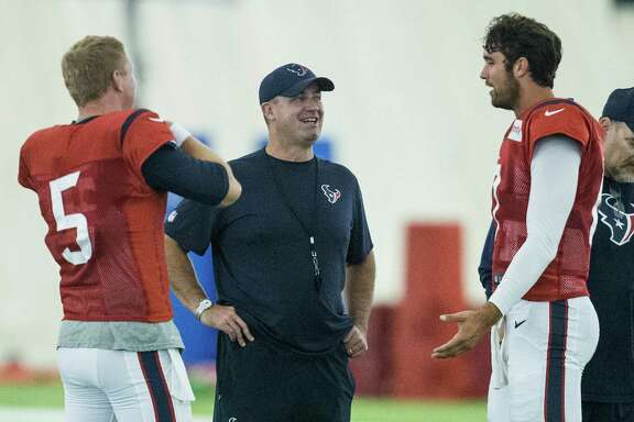 Houston Texans head coach Bill O'Brien talks to Houston Texans quarterbacks Brandon Weeden (5) and Brock Osweiler (17) during Texans training camp at Houston Methodist Training Center on Wednesday, Aug. 3, 2016, in Houston.