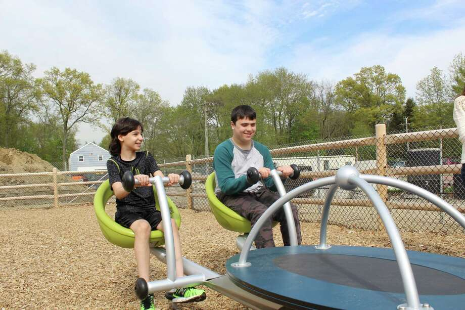 Youngsters enjoy the We-Saw, an inclusive adaptation to the see-saw for people of all abilities. The We-Saw was purchased with proceeds from previous races. Photo: Contributed / New Canaan News
