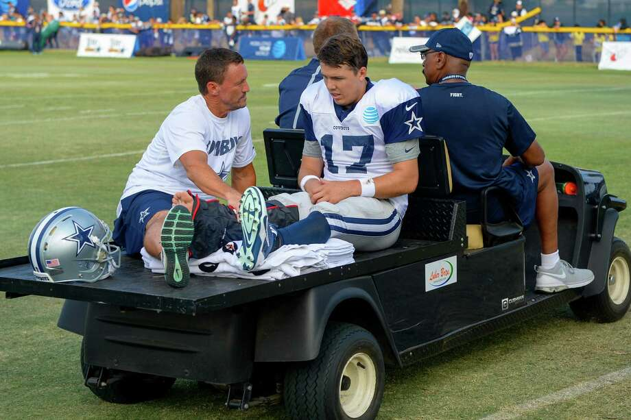 Dallas Cowboys associate athletic trainer Britt Brown, left, tends to quarterback Kellen Moore, right, as he's carted off the field with a broken right ankle during practice at the NFL football team's training camp in Oxnard, Calif., Tuesday, Aug. 2, 2016. (AP Photo/Gus Ruelas) Photo: Gus Ruelas, Associated Press / FR157633 AP