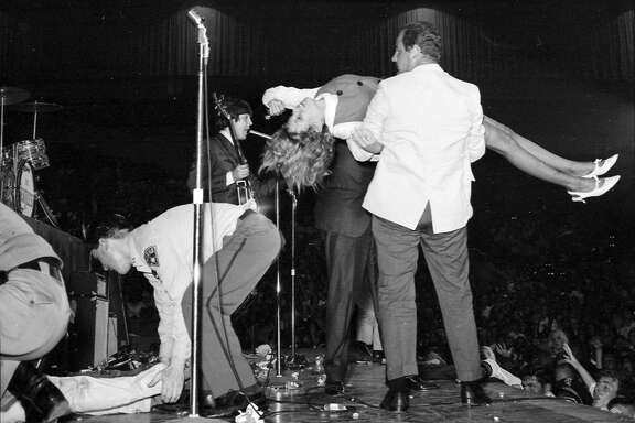 The Beatles play the Cow Palace on Aug. 31, 1965. Security had to carry fainting girls off the stage.