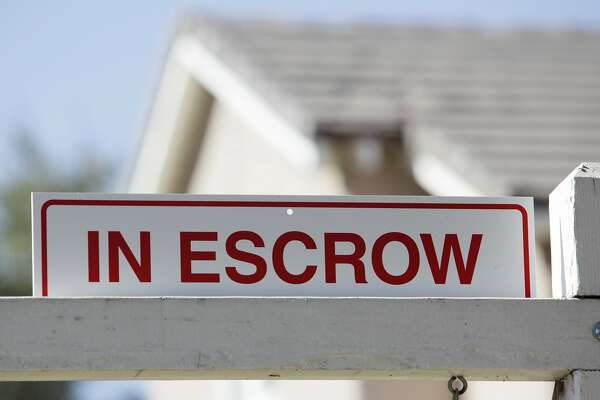 In this photo made Tuesday, Nov. 17, 2009, an 'in escrow' sign has been added to a 'for sale' sign outside a home in Los Angeles. The National Association of Realtors said Tuesday its seasonally adjusted index of sales agreements rose 3.7 percent from September to October to 114.1. (AP Photo/Reed Saxon)
