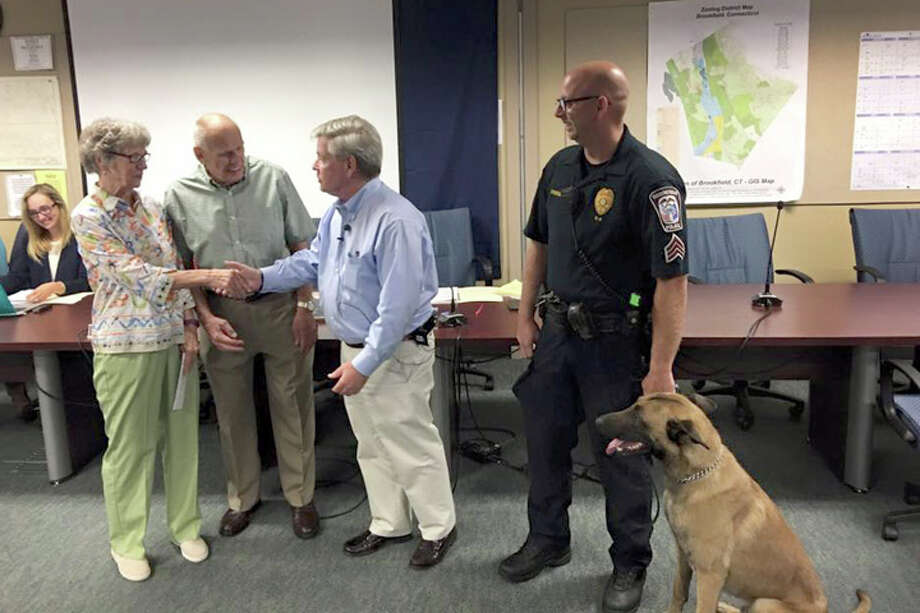 First Selectman Steve Dunn thanks Brookfield residents Ruth and Warren Malkin who donated $12,500 to the town to acquire the police department's new K9 unit Argo. Sgt. Jeff Osuch, right, is training with his new partner, who is expected to begin serving in October. Photo: Contributed Photo / Hearst Connecticut Media / The News-Times Contributed