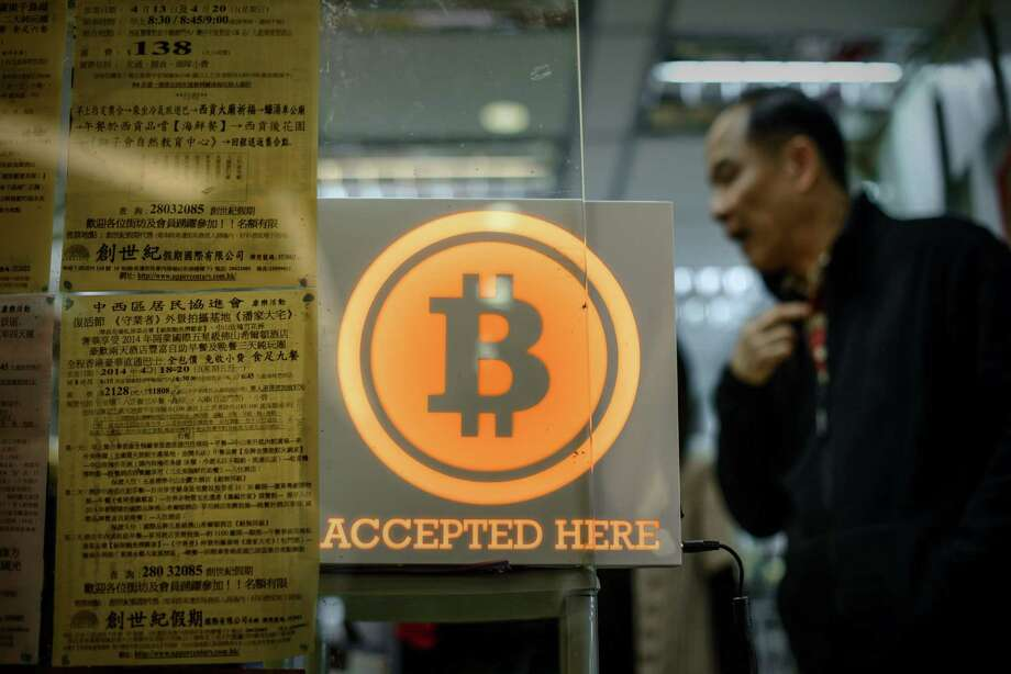 (FILES) This file photo taken on February 28, 2014 shows a man walking out of a shop displaying a Bitcoin sign during the opening ceremony of the first Bitcoin retail shop in Hong Kong. A major Hong Kong-based Bitcoin exchange on August 3, 2016 has suspended trading after 65 million USD in the virtual unit was reportedly stolen by hackers -- sending the digital currency plunging more than 20 percent.  / AFP PHOTO / PHILIPPE LOPEZPHILIPPE LOPEZ/AFP/Getty Images Photo: PHILIPPE LOPEZ, Staff / AFP/Getty Images / AFP or licensors