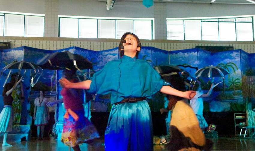 Zachary Rood plays the part of Agwe, the god of water, as students at Scofield Magnet Middle School present