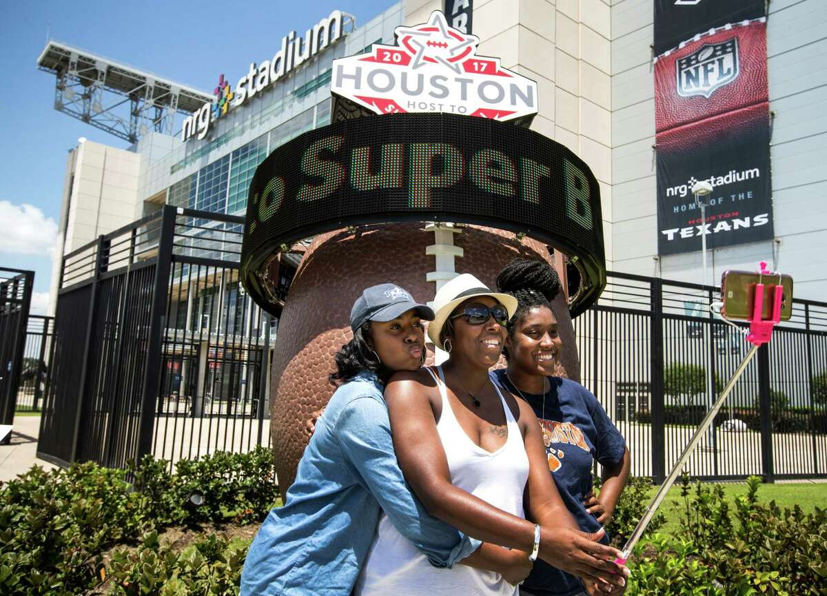 From left, Brittney Lee, Tamika Givens and Destiny Lee pose for a selfie next to the Super Bowl LI countdown clock outside NRG Stadium. The game will be Feb. 5.