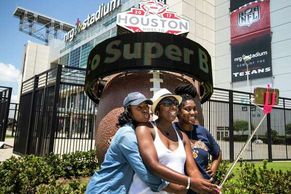 From left, Brittney Lee, Tamika Givens and Destiny Lee pose for a selfie Wednesday next to the Super Bowl LI countdown clock outside NRG Stadium. The game will be Feb. 5.