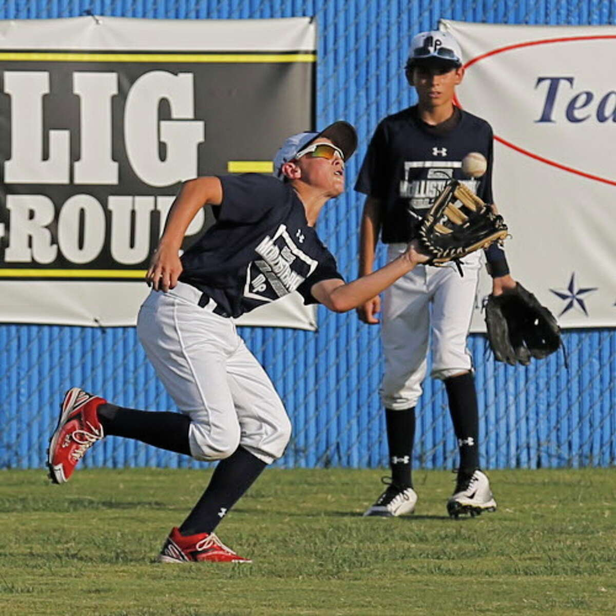 McAllister Park Little League's Zane Raba (left) makes an outfield catch beside teammate Teagan Peeples during practice on Tuesday, July 28, 2015. MPLL also celebrated their state championships in three age divisions of little league baseball with a group photo session. The 11-12 year-old squad will now continue to regional play in Waco and if successful there will move onto the Little League World Series in Willamsport, Penn. MPLL offers many opportunities for boys and girls to play baseball or softball. Fall registration begins Aug. 1. They also offer a Spring Challenger League for special needs kids which starts in March. The boys will play Louisiana in Waco on Aug. 7. (Kin Man Hui/San Antonio Express-News)