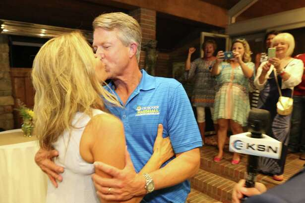 Dr. Roger Marshall kisses his wife Laina after finding out he won McPherson County during a watch party Tuesday, Aug. 2, 2016, in Great Bend, Kan. The doctor backed by agriculture and business groups has defeated U.S. Rep. Tim Huelskamp in the Republican primary to represent a district spanning much of central and western Kansas. (Travis Morisse/The Hutchinson News via AP)