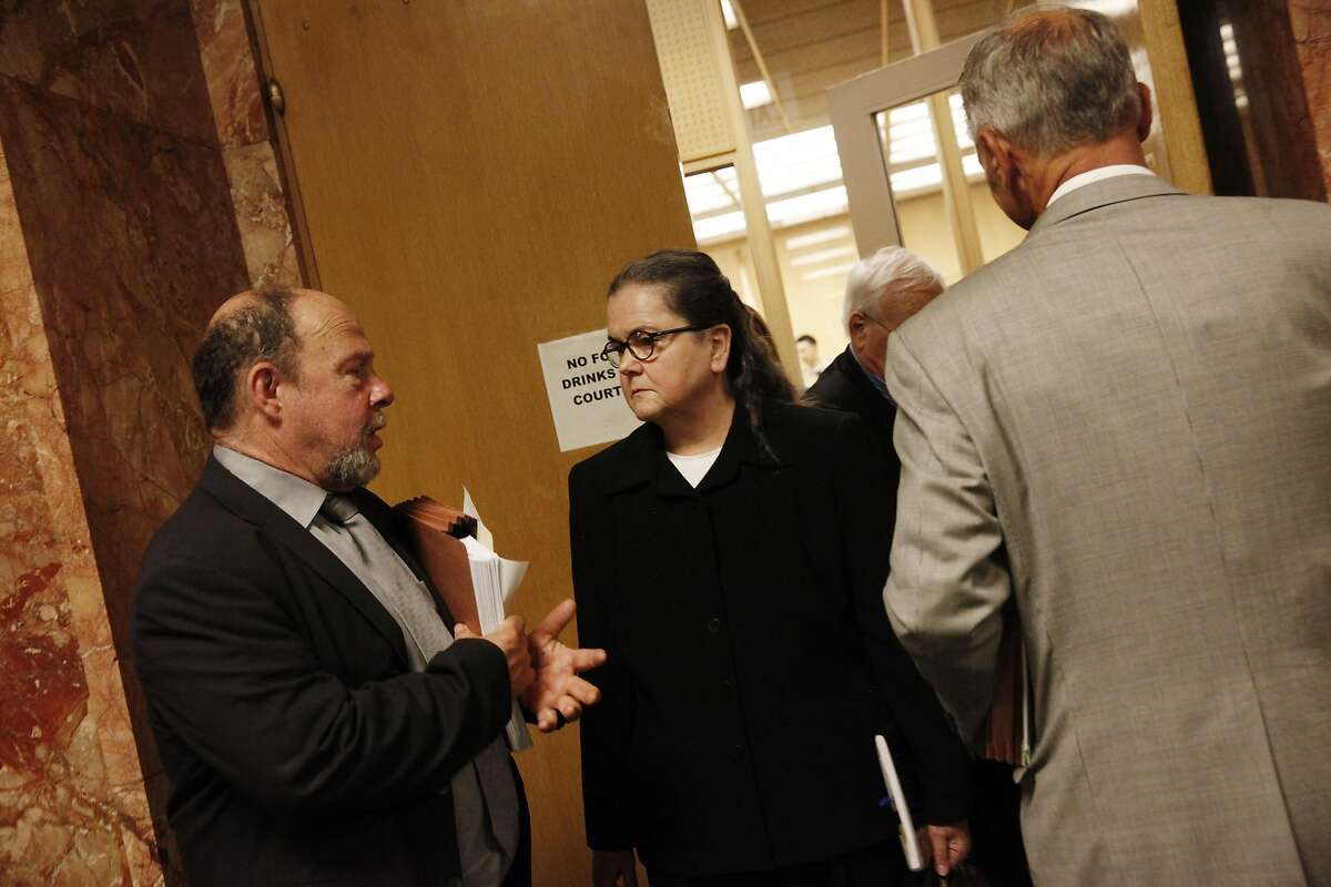 Trish Bascom (second from left), who was San Francisco Unified School District associate superintendent of student support services, talks with her attorney Stuart Hanlon (left) outside of Department 11 after the arraignment of the six former and current San Francisco Unified School District employees charged for allegedly misappropriating $15 million in public funds on Tuesday, May 21, 2013 in San Francisco, Calif.