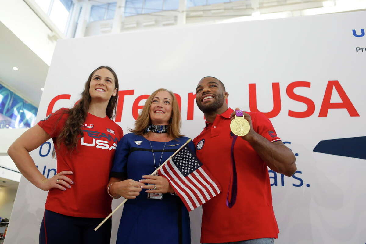A United employee takes a picture with Olympic athletes Adeline Gray (left), a three-time world champion wrestler, and Jordan Burroughs (right), who won gold in the 2012 Olympics in London, before over one hundred Team USA athletes, coaches and staff prepare to board their flight to Rio at Bush Intercontinental Airport, Wednesday, Aug. 3, 2016, in Houston. United is a sponsor for Team USA and expects to fly 1300 athletes, coaches and team staff to Rio for the Olympic and Paralympic games.