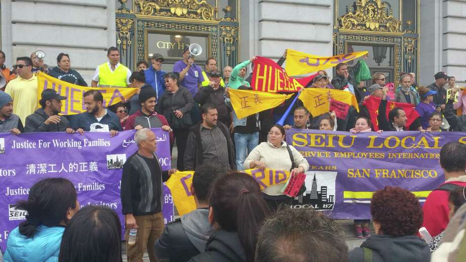 Janitors wait outside of San Francisco's city hall amid contract negotiations with their union representatives and cleaning companies that employ them on Wednesday, August 3, 2016. The workers received a pay raise, union officials said.