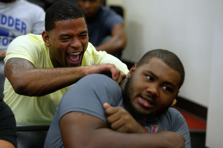 Lamar linebacker Mike Hargis jokes around with defensive lineman Omar Tebo before a team meeting on Wednesday afternoon. Tebo recently gained national attention with a viral video of the team hyping him up to squat 640 pounds.  Photo taken Wednesday 8/3/16 Ryan Pelham/The Enterprise Photo: Ryan Pelham / ©2016 The Beaumont Enterprise/Ryan Pelham