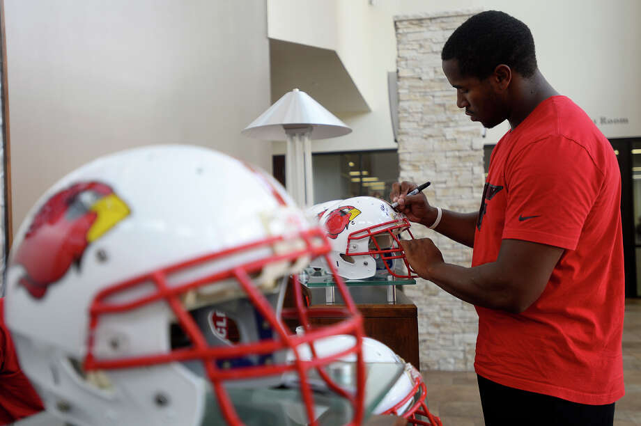 Lamar's senior tight end DeAndre Jennings signs helmets as players report for a team meeting on Wednesday afternoon.  Photo taken Wednesday 8/3/16 Ryan Pelham/The Enterprise Photo: Ryan Pelham / ©2016 The Beaumont Enterprise/Ryan Pelham