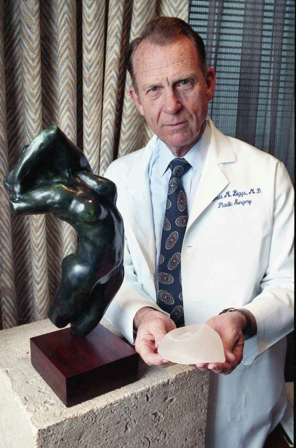 Dr. Thomas Biggs, a Houston plastic surgeon, photographed on Feb. 3, 1992, displays a silicone-gel breast implant. In the early 1990s, the FDA set a moratorium on silicone gel implants, and saline filled implants rose in popularity. As a resident with Baylor College of Medicine, Biggs helped on the team that performed the first breast augmentation surgery using the implants. Biggs also took care of the test case patient, a dog named Esmeralda who got a biscuit-sized implant before they tried the device on human patients.
