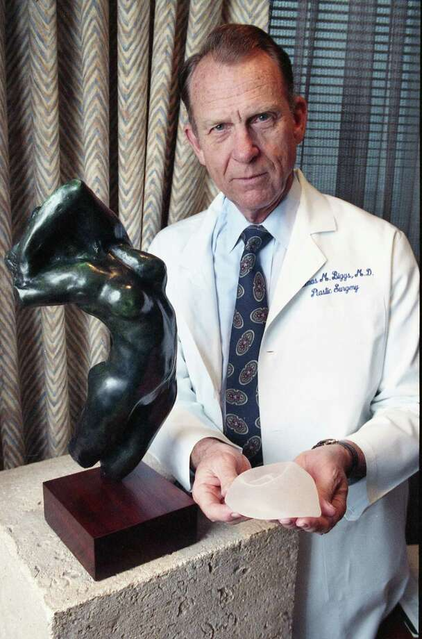 Dr. Thomas Biggs, a Houston plastic surgeon, photographed on Feb. 3, 1992, displays a silicone-gel breast implant. In the early 1990s, the FDA set a moratorium on silicone gel implants, and saline filled implants rose in popularity. As a resident with Baylor College of Medicine, Biggs helped on the team that performed the first breast augmentation surgery using the implants. Biggs also took care of the test case patient, a dog named Esmeralda who got a biscuit-sized implant before they tried the device on human patients. Photo: Richard Carson, HC Staff / Houston Chronicle