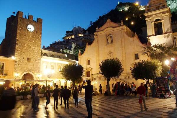 Locals and travelers fill Piazza IX Aprile, in front of the San Giuseppe church, in the coastal resort town of Taormina, Sicily.