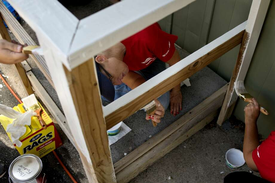 Dow Chemical employees from left: Nicole Van Horn, Jodi Kridler and Cheryl Conner paint the hand-railing on the house located at 1306 Fournie St in Midland on Wednesday as part of the 2016 Neighborhood Revitalization. Volunteers worked in Midland the week of August 1, doing home repairs ranging from painting to roof replacement on 25 homes in the area. Photo: Brittney Lohmiller/Midland Daily News/Brittney Lohmiller