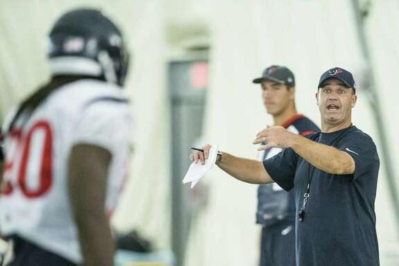 Houston Texans head coach Bill O'Brien talks to outside linebacker Jadeveon Clowney (90) during a special teams drill at Texans training camp at Houston Methodist Training Center on Wednesday, Aug. 3, 2016, in Houston.