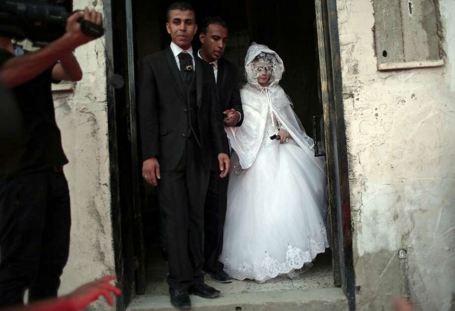 In this Saturday, July 30, 2016 photo, Palestinian groom Saed Abu Aser, 22, walks with his bride, Falasteen, out of her family house to the wedding hall to celebrate their wedding, in Gaza City. Weddings have emerged as a welcome celebration that slices through the often morose mood in the Gaza Strip, a Palestinian coastal territory run by the militant group Hamas. For both poor and well-off Gazans, weddings are a days-long, lavish affair of parties and dancing. (AP Photo/ Khalil Hamra) Photo: Khalil Hamra, Associated Press