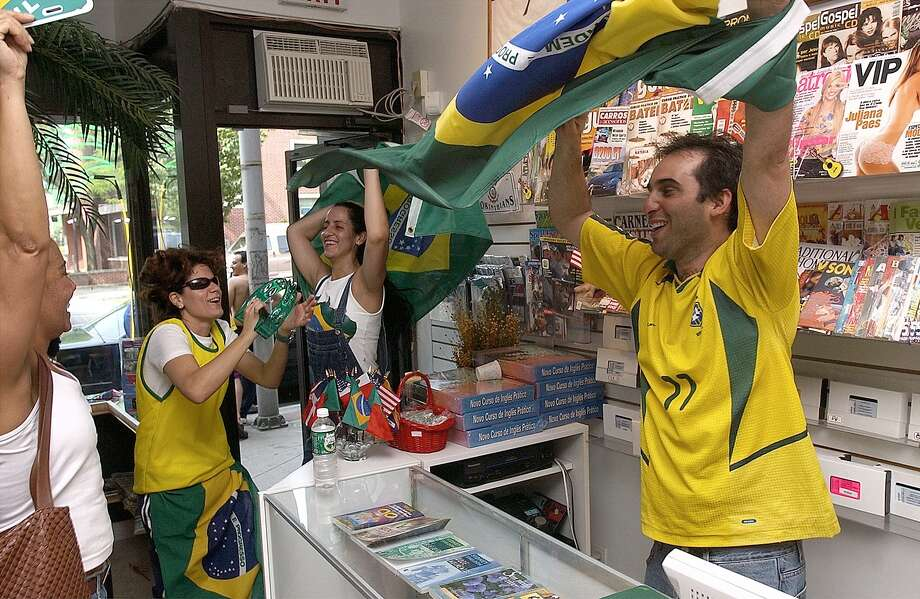 Edward Soares, right, waves the brazilian flag in his store Osomodobrasil on main street.  Customers celebrate with him after brazil won their last world cup game that propelled them into the finals.  Also in the pictrue is Cristiane Ogiveira-Pe Nort (with tamborine) who also works at the store.