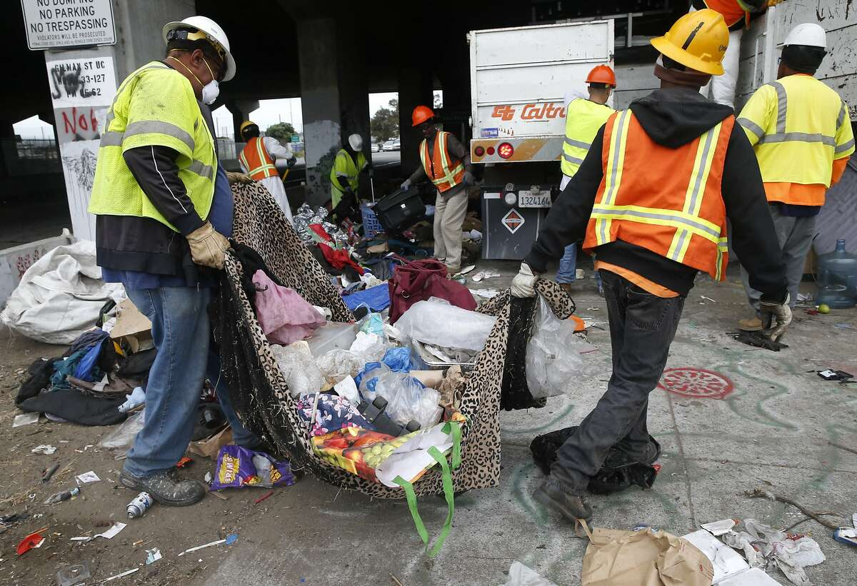 A Caltrans crew removes debris near the eastbound on-ramp after CHP officers clear out a homeless encampment on Gilman Street below Interstate 80 in Berkeley, Calif. on Thursday, Aug. 4, 2016. Caltrans will be erecting reinforced fencing to prevent the homeless from camping at the site below the freeway.
