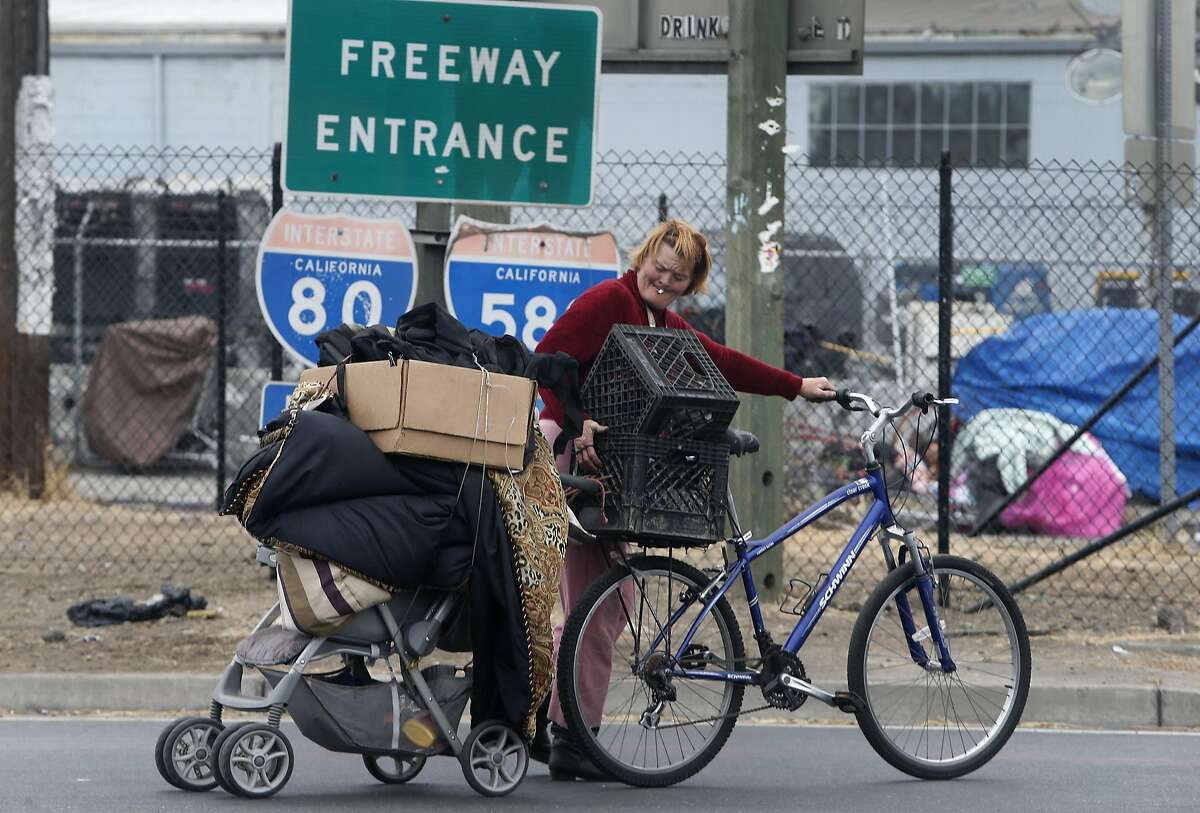 Vicky Pfeifer rolls her belongings across the eastbound on-ramp after Caltrans and CHP officers clear out a homeless encampment on Gilman Street below Interstate 80 in Berkeley, Calif. on Thursday, Aug. 4, 2016. Caltrans will be erecting reinforced fencing to prevent the homeless from camping at the site below the freeway.