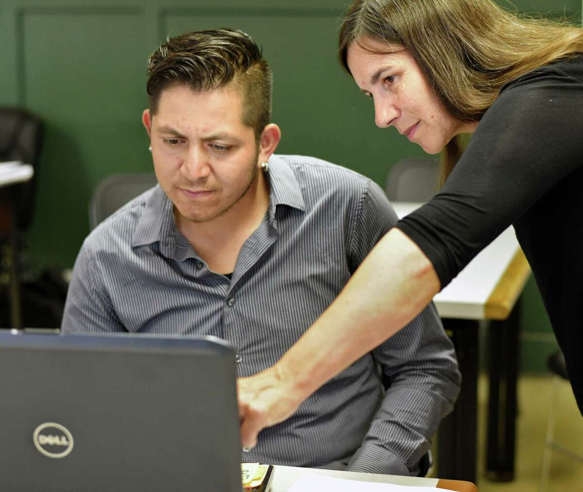 Track worker Julio Castro, left, and Saratoga County EOC instructor Joan Odess review photos on a laptop as they prepare for an upcoming photography exhibit at the Saratoga Race Course Thursday July 28, 2016 in Saratoga Springs, NY. (John Carl D'Annibale / Times Union)