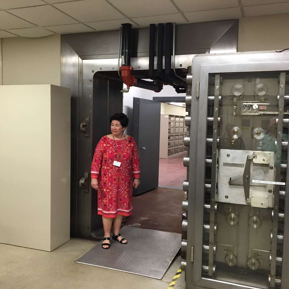 Juliette Moke, coordinator with the Bexar Heritage Department, stands at the entrance of an underground vault to be leased from the county by Texas A& University-San Antonio. The vault will be secured with an inner door, shown in the background, and not the heavy door to the right that was used by the Federal Reserve to secure billions of dollars in cash. Photo: Scott Huddleston / Staff / Scott Huddleston / Staff