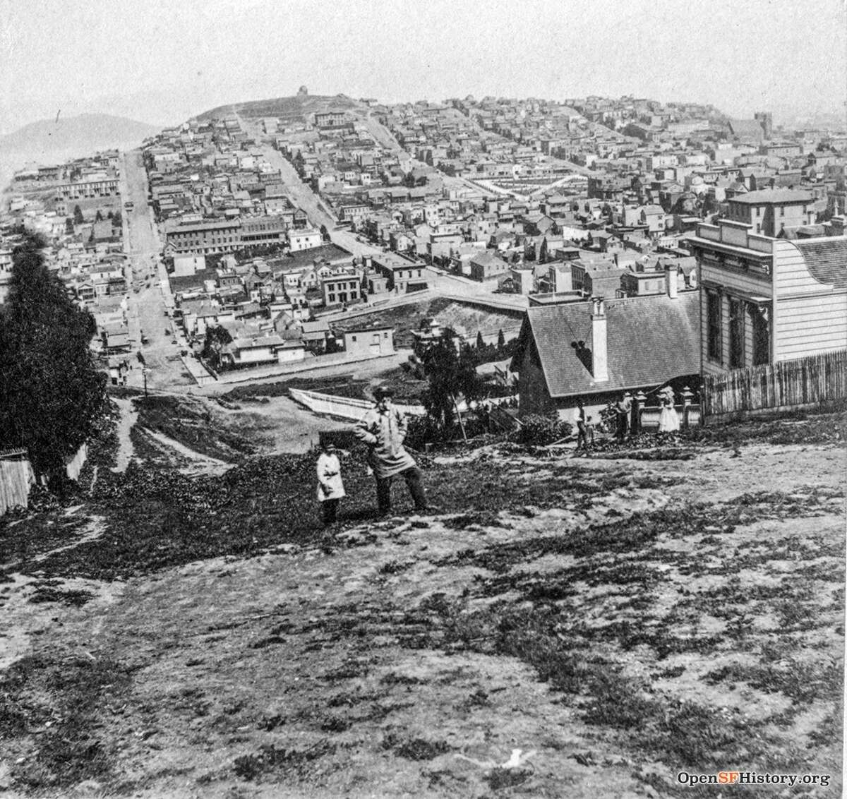Lombard Street near Leavenworth - the future site of crooked block. Houses, streets, and undeveloped area. Man and child standing in foreground. Angel Island in the distance. Kilburn Brothers, Littleton, N.H. Courtesy of OpenSFHistory.org.