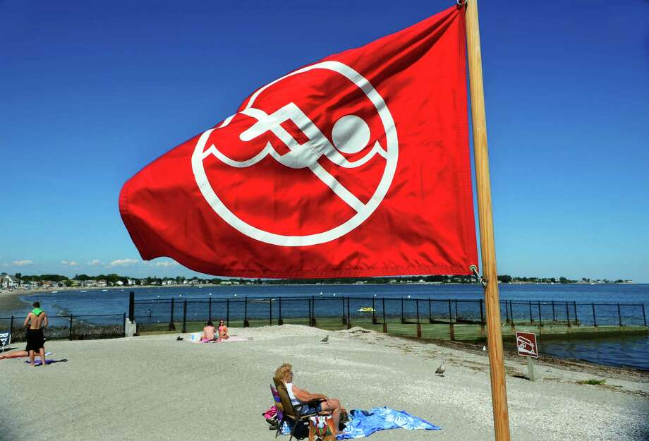 A red no swimming flag is displayed to warn beachgoers at Silver Sands State Park in Milford, Conn., on Thursday Aug. 4, 2016. The park remains closed to swimmers for a second day, due to the presence of bacteria in the water. Photo: Christian Abraham / Hearst Connecticut Media / Connecticut Post