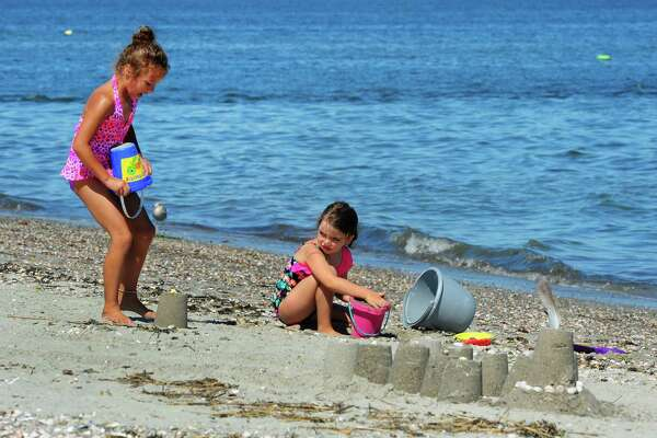 Tessa Bundy, 7, from PA and visiting family in Derby and Gabriella Plante, 6, of Seymour, play on the beach at Silver Sands State Park in Stratford, Conn., on Thursday Aug. 4, 2016. The park remains closed to swimmers for a second day, due to the presence of bacteria in the water.
