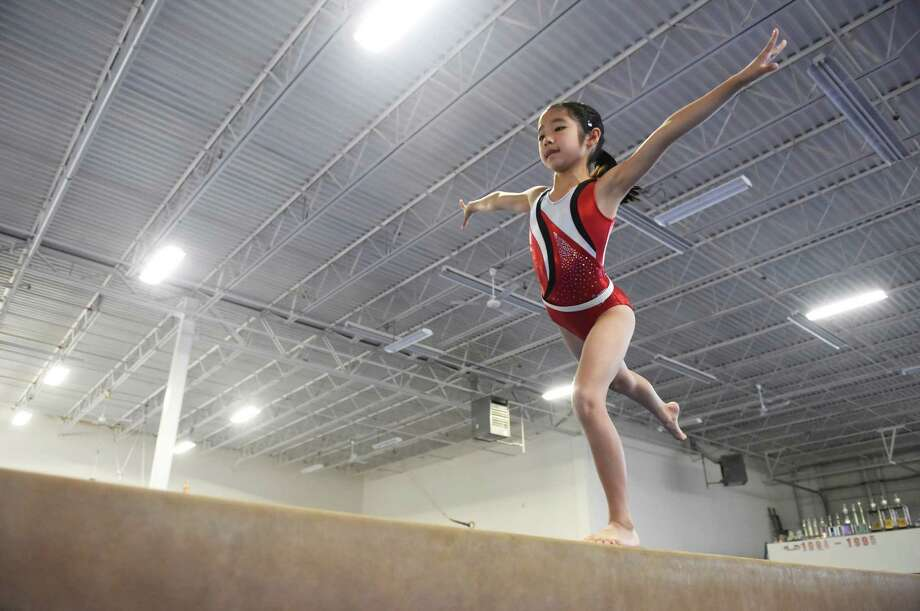 Greenwich gymnast Claire Yee, 9, performs a routine on the beam at Arena Gymnastics in Stamford, Conn. Thursday, Aug. 4, 2016. Yee and others who train at Arena Gymnastics are looking forward to watching Team USA gymnastics compete in the Rio Olympic Games. Photo: Tyler Sizemore / Hearst Connecticut Media / Greenwich Time